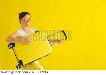 Smiling Woman In Sunglasses Fooling Around And Holding A Suitcase Like A Guitar On A Yellow Backgrou