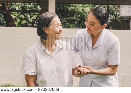 Portrait Of Happy Smiling Nurse Helping Mature Elderly  Standing And Walking In A Nursing House. Nur