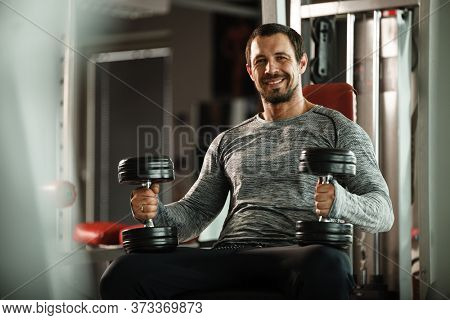 Fitness in gym, sport and healthy lifestyle concept. Handsome athletic man in grey shirt making exercises. Bodybuilder male model training biceps muscles with dumbbell.