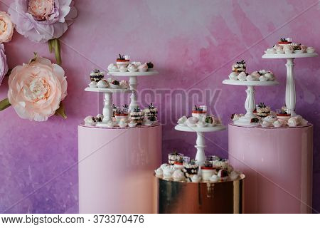 Catering Sweets With Desserts Decorated With Fruits At The Pink Background With Copyspace. Dessert.