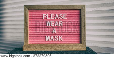 Please wear a mask pink sign at business store entrance message. Obligatory wearing of COVID-19 protection face cover.