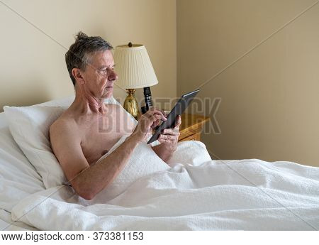 Senior Retired Caucasian Man Lying In Adjustable Bed On Incline. He Is Reading And Scrolling On Digi