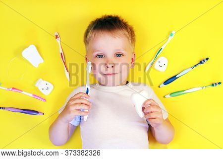 Happy Boy Child Kid With Toothbrushes  On Yellow Background. Teeth Cleaning, Oral Care, Dental Hygie