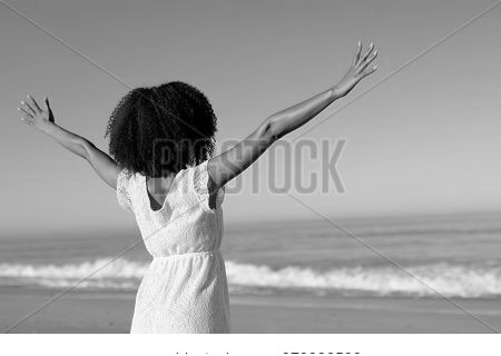 A rear view of a happy, attractive mixed race woman enjoying free time on beach on a sunny day, wearing a white dress, sun shining on her face with her arms outstretched. Relaxing summer vacation.