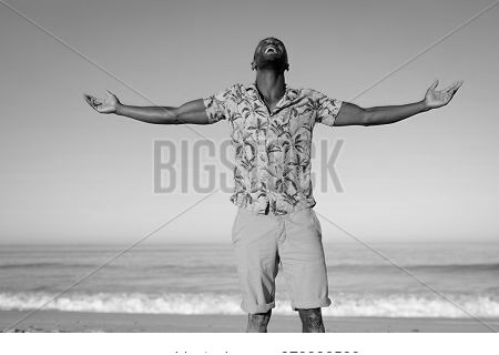 A happy, attractive African American man enjoying free time on beach on a sunny day, wearing a Hawaiian shirt, sun shining on his face with his arms outstretched. Relaxing summer vacation.