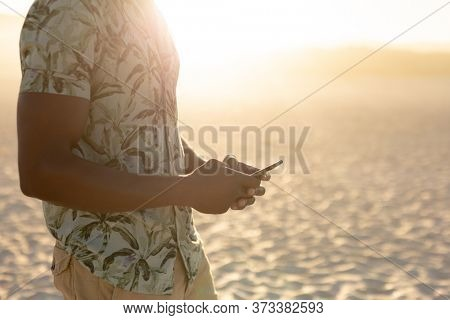 An African American man enjoying free time on beach on a sunny day, standing on sand with sun shining behind him, wearing a Hawaiian shirt, using his smartphone. Relaxing summer vacation.