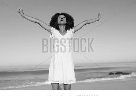 A happy, attractive mixed race woman enjoying free time on beach on a sunny day, wearing a white dress, sun shining on her face with her arms outstretched. Relaxing summer vacation.