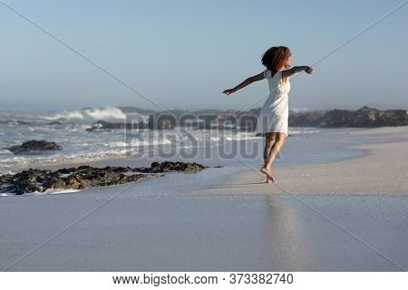 A happy, attractive mixed race woman with her arms outstretched enjoying free time on beach on a sunny day, wearing a white dress, walking, sun shining on her face. Relaxing summer vacation.