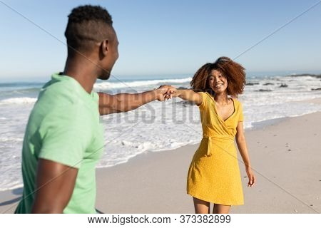A mixed race couple enjoying free time on beach on a sunny day together, holding hands, having fun and laughing with sun shining on their faces. Relaxing summer vacation.
