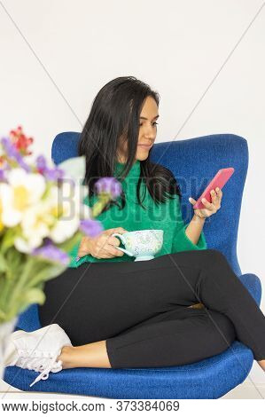 Lovely Young Woman Using Her Smartphone In Your Living Room