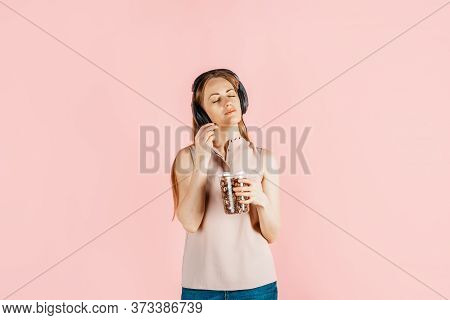 Fast Food, Movie Food, Popcorn. Passion For Music. Girl In Headphones On A Pink Background Holds Pop