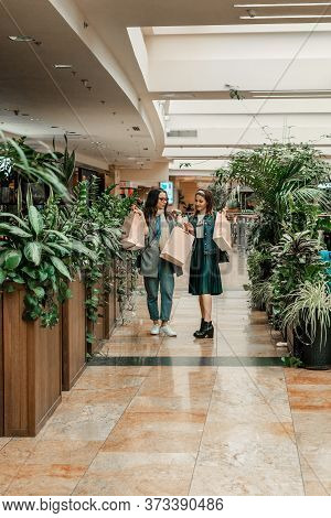 Trade, Buyers. Two Beautiful Girls Make Purchases In A Shopping Center, Go Shopping. Green Hothouse