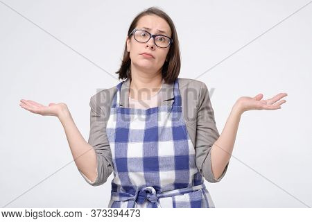 Woman In Doubt Doing Shrug Showing Open Palms Having No Idea How To Cook.