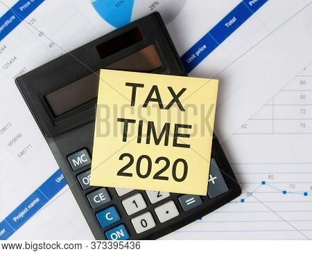 Tax Time 2020 - Phrase On Paper Sticker. Tax Time 2020 Concept, Top View, Calculator, Financial Grap