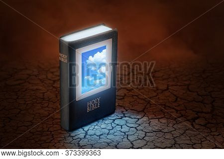 Holy Bible With A Window On The Cover Through Which Blue Sky Can Be Seen, Standing On A Dry And Crac