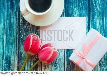 Flat Lay Photo With Coffee Cup, Gift Box And Red Tulips On Wooden Background. Beautiful Mother's Day
