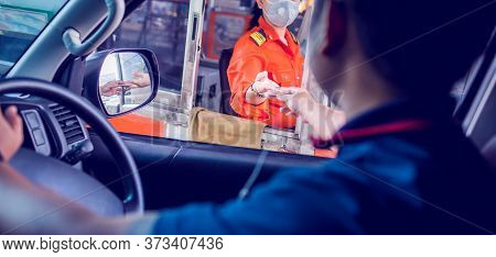Selective Focus To Driver Pay For The Expressway. Man Pays Money To A Cashier For A Toll Road Toll G