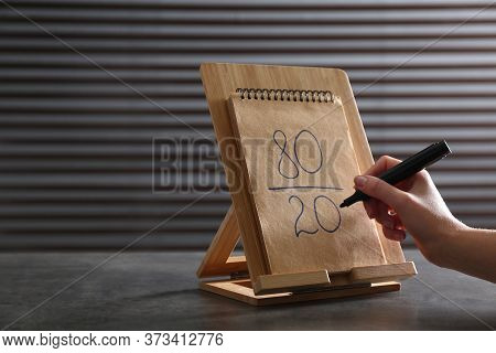 Woman Writing 80/20 Rule Representation In Notebook At Grey Table, Closeup. Pareto Principle Concept