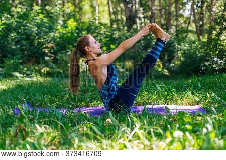 Young Woman Doing Yoga Exercises In Summer City Park.