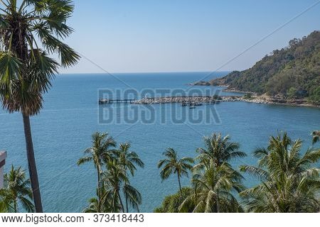 A Stony Pier In A Small Harbor With Simmering Turquoise Sea. Green Coconut Trees Swaying  In The Gen