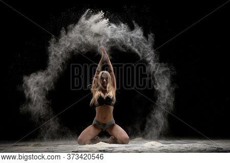 Slim Female Dancer Kneeling And Throwing Dust