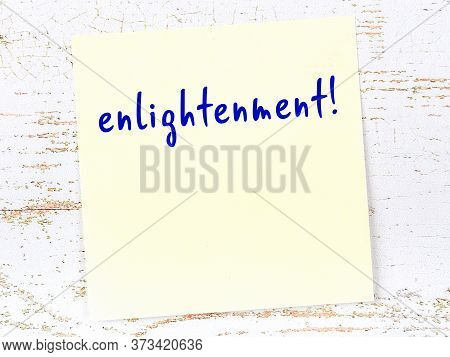 Concept Of Reminder About Enlightenment. Yellow Sticky Sheet Of Paper On Wooden Wall With Inscriptio