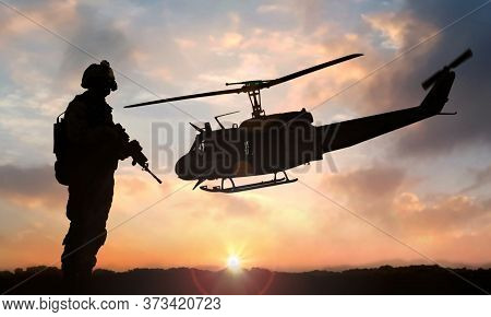 Military Soldier Standing On Open Field With Automatic Weapon In Front Of Helicopter At Sunset