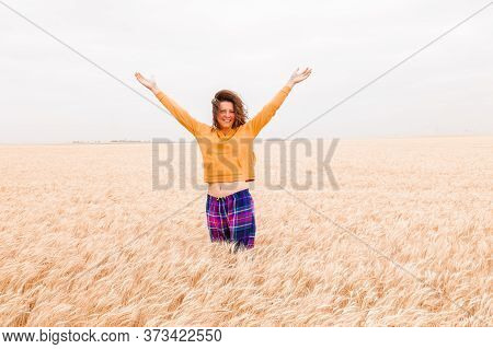 Beautiful Woman Enjoying Nice Rural Landscape While Traveling. Girl Spread Her Arms On A Golden Whea