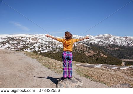 Beautiful Woman Enjoying Nice Mountain Landscape While Traveling. Girl Spread Her Arms On Top Of Mou