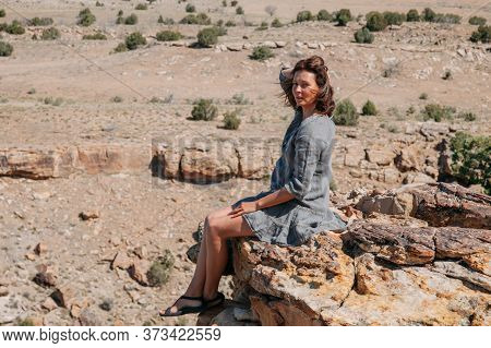 Beautiful Brunette Woman Enjoying Nice Mountain Landscape While Traveling. Young Woman In Gray Dress