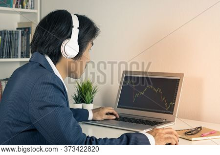 Young Asian Forex Trader Or Investor Or Businessman In Suit Wear Headphone And Trading Forex Or Stoc
