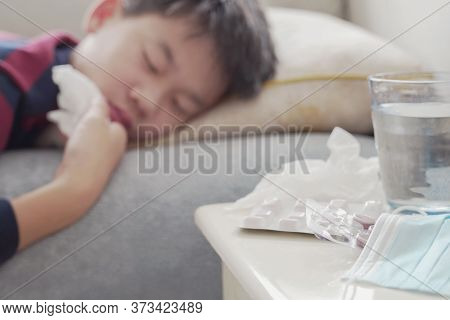 Chewable Pills, Mask And Glass Of Water Next To Mixed Asian Sick Preteen Boy Resting On Sofa At Home