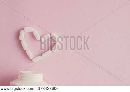 White Tablets And Pills In Heart Shape And Bottle For Cardiology Heart Disease, Prebiotics And Probi