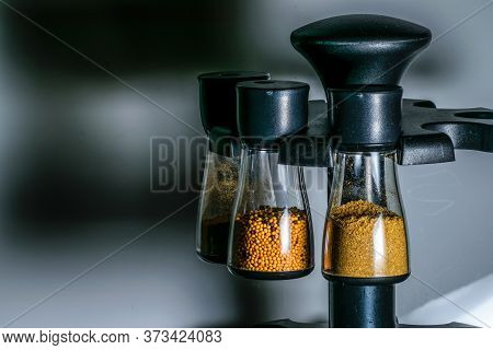 Transparent Containers Containing Mustard Seeds, Coriander Powder And Cumin Powder