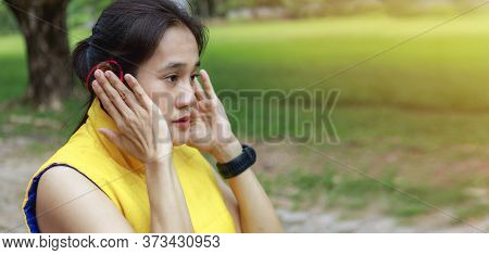 Asian Woman Long Hair Wearing Yellow Jacket Relax  Listening To Music At Park After Running. Young W