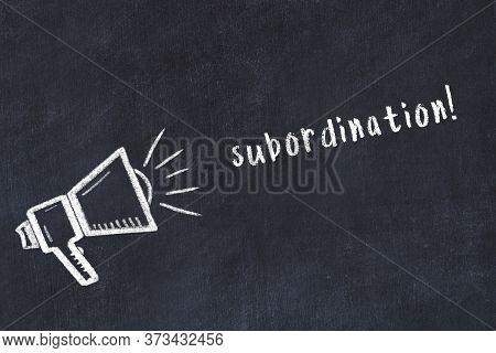 Chalk Drawing Of Loudspeaker And Handwritten Inscription Subordination On Black Desk