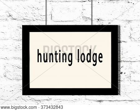 Black Wooden Frame With Inscription Hunting Lodge Hanging On White Brick Wall