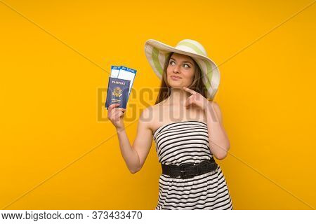 Joyful Young Woman In A Straw Hat And A Striped Dress Is Holding Airline Tickets With A Passport On