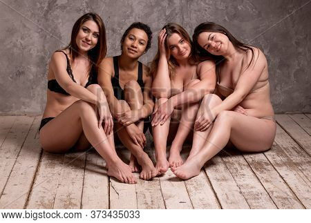 Beautiful Overweight And Slim Women In A Beige And Black Swimsuit On A Gray Background. Body Positiv