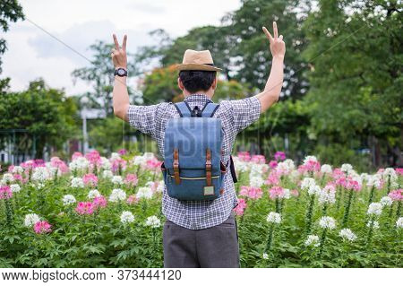 Young Man Tourists Backpack Are Standing For Victory Performances Hand Sign. At Spider Flower Garden