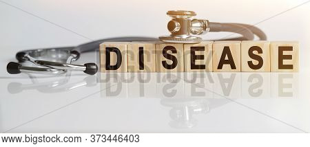 Disease The Word On Wooden Cubes, Cubes Stand On A Reflective White Surface, On Cubes - A Stethoscop
