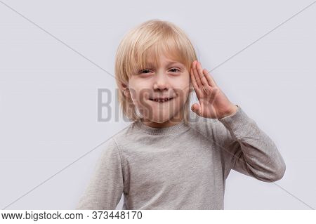 Portrait Of Cute Blond Boy On White Background. Child Holds Hand Of Face And Grins.