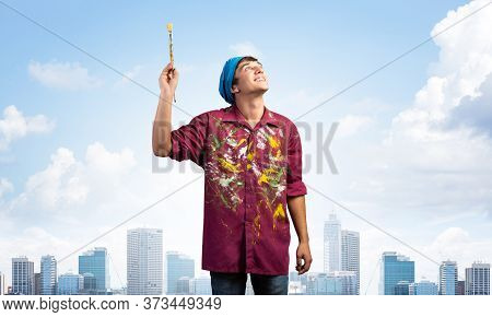 Young Painter Artist Holding Paint Brush Overhead. Portrait Of Decorator Looking Upwards On Blue Sky