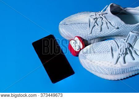 Sneakers, Phone, Earphones Stand In A Charge For Earphones On A Blue Background Close-up