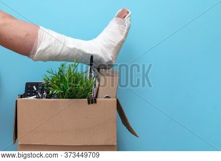 Leg In Plaster Over A Box Of A Fired Man From Work On A Blue Background. The Concept Of Dismissal Du