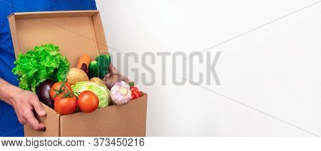 Delivery Man Of Fresh Vegetables In A Blue Uniform On A White Background. Photo For Website Banner