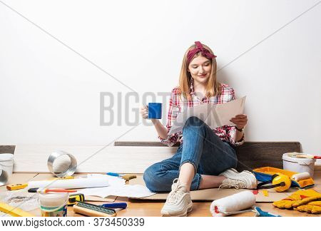 Happy Pretty Girl Sitting On Floor With Paper Blueprint. Home Remodeling And House Interior Redesign