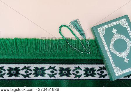 Muslim Islamic Faith Concept. Koran Book, Green Rosary, Green Mat Pray. Neutral Beige Background. La