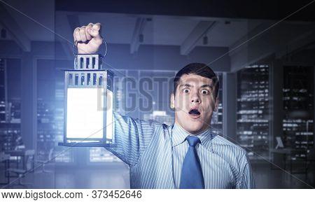 Horrified Businessman Holding Glowing Lantern On Background Office Interior. Emotional Corporate Emp