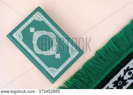 Muslim Islamic Faith Concept Koran Book , Green Rosary, Green Mat Pray . Neutral Beige Background. L